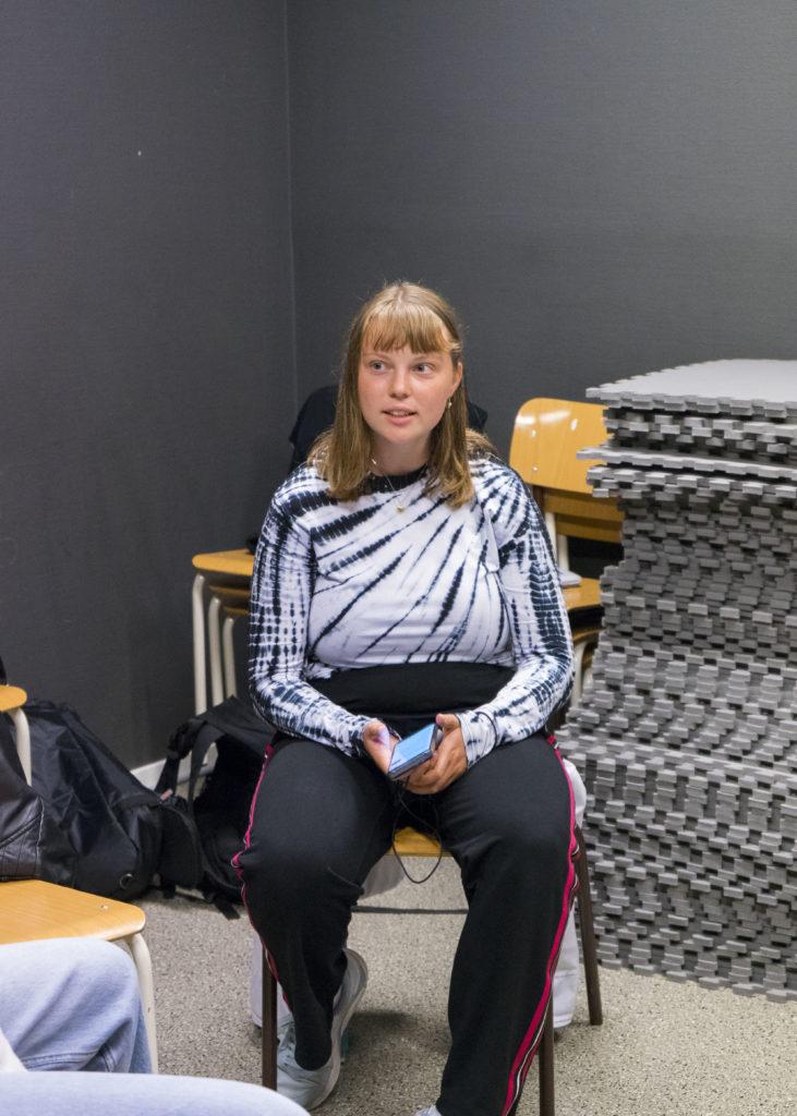 Ung tjej sitter på en stol och sjunger.