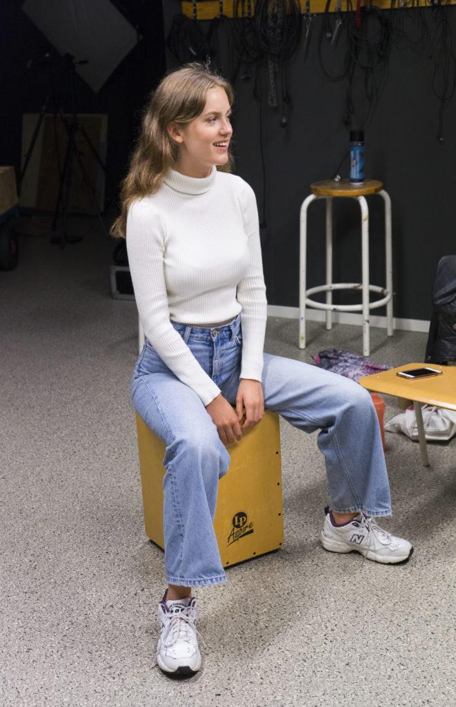 Ung tjej sitte roch spelar på en cajóntrumma