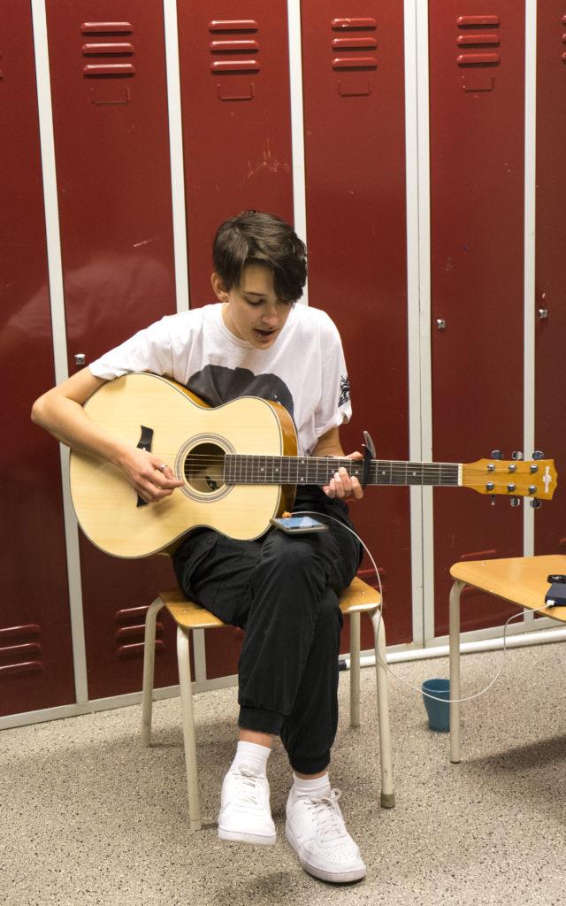 Ung kille spelar på akustisk gitarr.