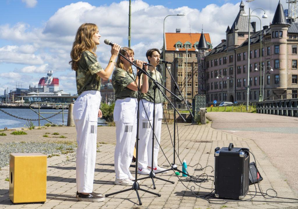 Tre ungdomar sjunger acapella utomhus