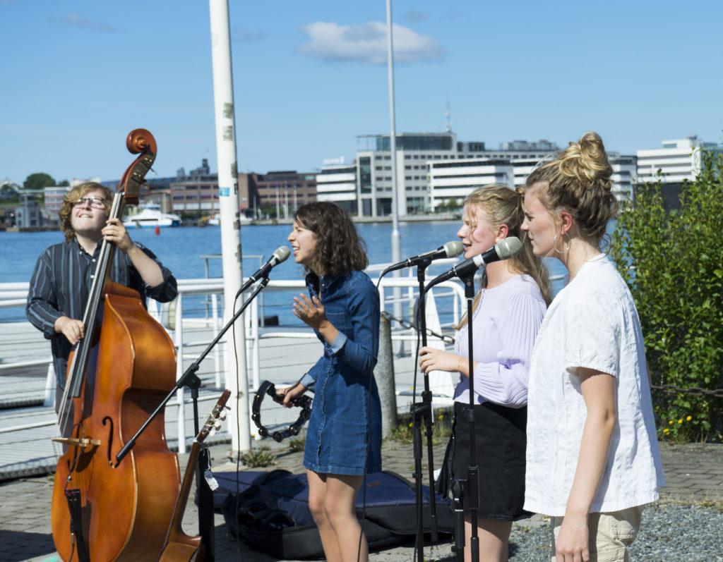 Fyra ungdomar spelar musik och sjunger utomhus.