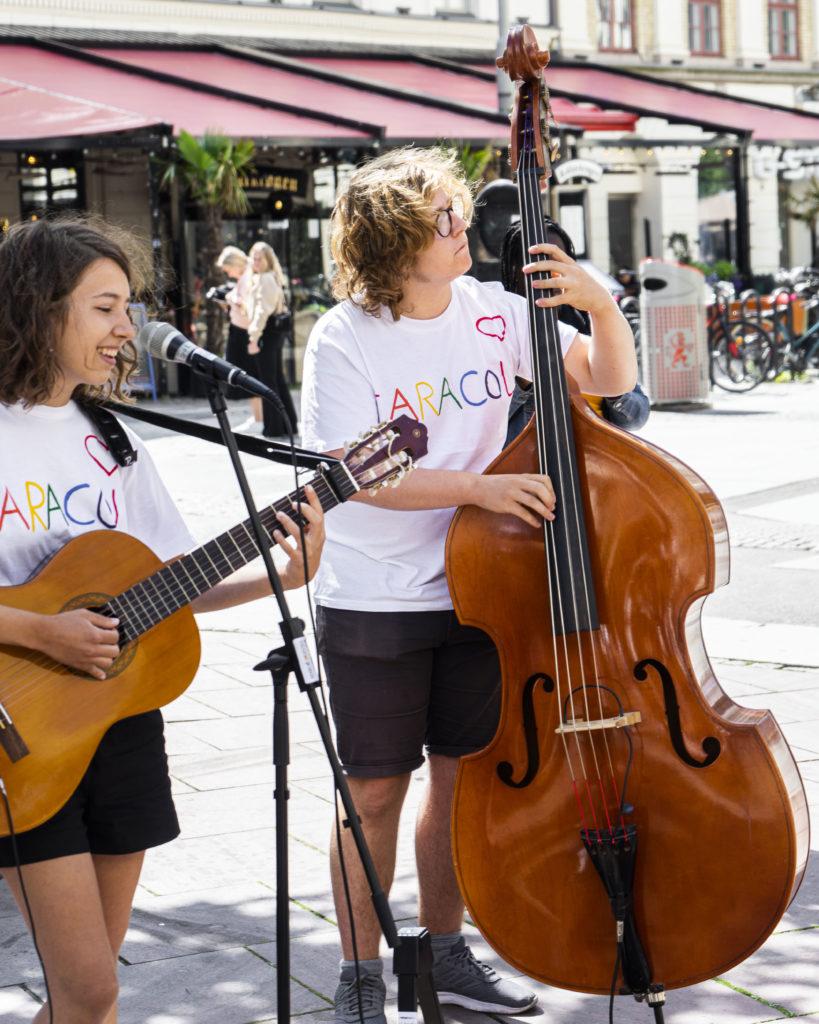 Två ungdomar spelar musik utomhus. Ungdom till vänster spelar akustiskt gitarr och sjunger, ungdom till höger spelar kontrabas.