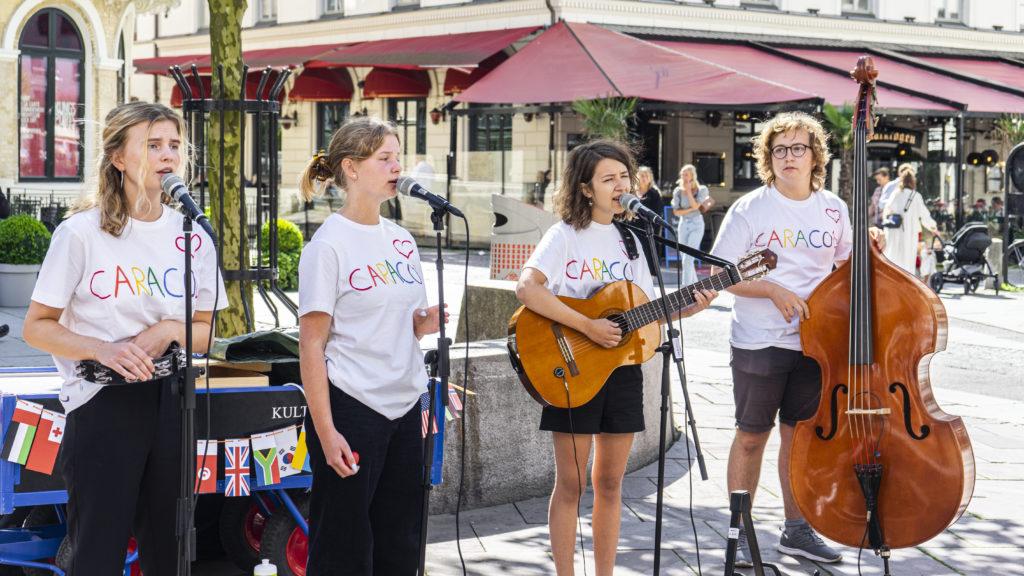 Fyra ungdomar sjunger och spelar musik utomhus